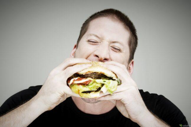 hombre caucasico comiendo una hamburguesa