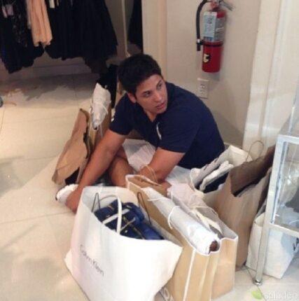 sujeto sentado al rededor de bolsas de compras